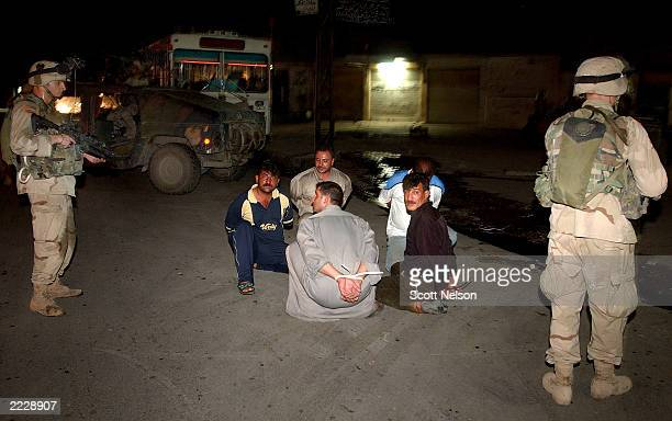 S Army 101st Airborne Third Battalion 502nd Infantry soldiers stand guard over a group of Iraqi men detained for questioning during an overnight raid...