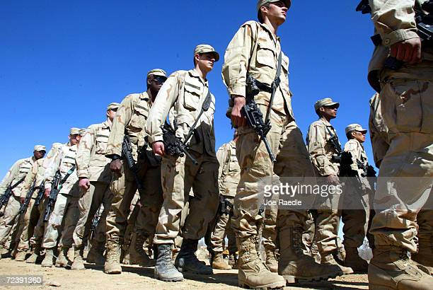 Army 10th Mountain Division soldiers march in formation March 13, 2002 after receiving a pep talk from Col. Frank Wiercinski at the Bagram Air Base...