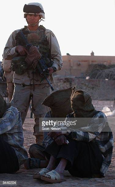 S Army 1st Battalion 14th regiment of the 25th Infantry Division Specialist Reynaldo Gonzales from San Diego CA guards detainees suspected of being...