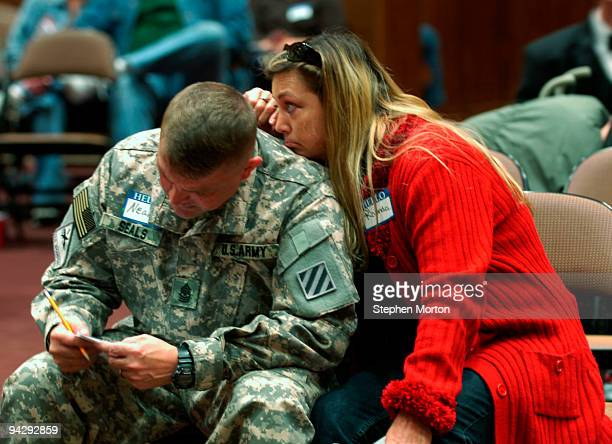 Army 1st Heavy Brigade Combat Team Sgt. Major Neal Seals fills out commitment card while his wife Rhonda waits for him to finish as part of the Coin...