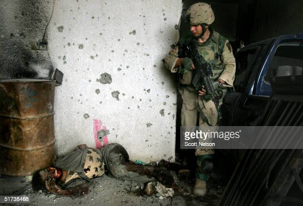 S Army 1st Infantry Division 2nd Battalion2nd Regiment Sergeant Randy Laird from Lake Charles Louisiana walks past the body of a slain Iraqi...