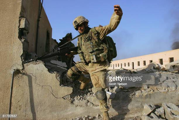 S Army 1st Infantry Division's 2nd Battalion2nd Regiment Specialist Josh Harrill from Greenbay Wisconsin leaps through an opening in a broken wall...
