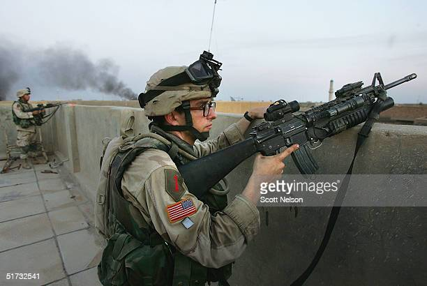 S Army 1st Infantry Division's 2nd Battalion2nd Regiment Specialist James Reichrath from Ava Illinois watches for enemy activity from atop a captured...