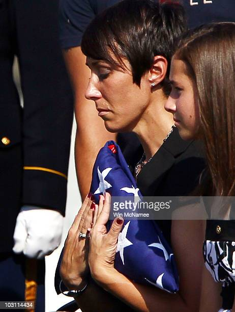 Army 1st Sgt. Jennifer Laredo holds the American flag that covered the caseket of her husband, Staff Sgt. Edwardo Loredo, during his burial service...