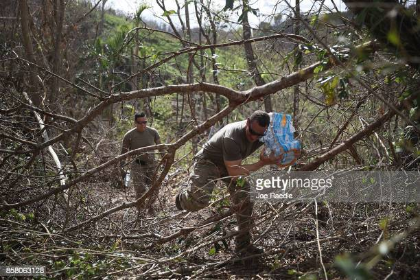 S Army 1st Special Force Command SFC Antonio Santini makes his way through downed trees as he helps deliver food and water to hurricane survivors in...
