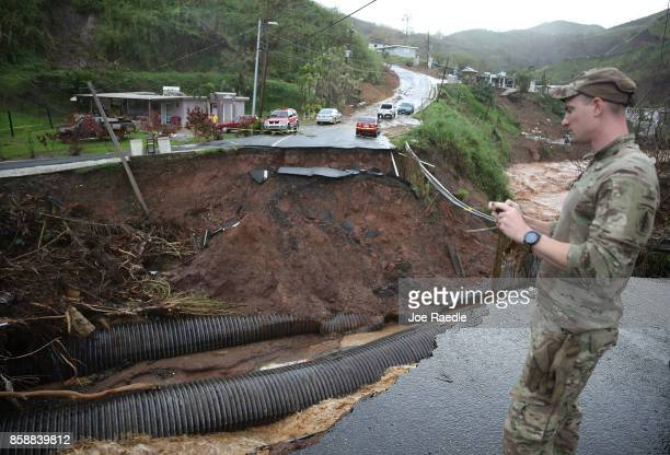 Army 1st Special Force Command Sgt. Kenneth McAnally surveys a section of a road that collapsed and continues to erode days after Hurricane Maria...