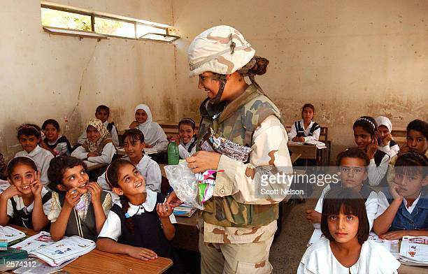 S Army 325th Military Intelligence Seargent Angela Vasquez from Granite City IL distributes candy to Iraqi schoolgirls during an October 9 2003 civil...
