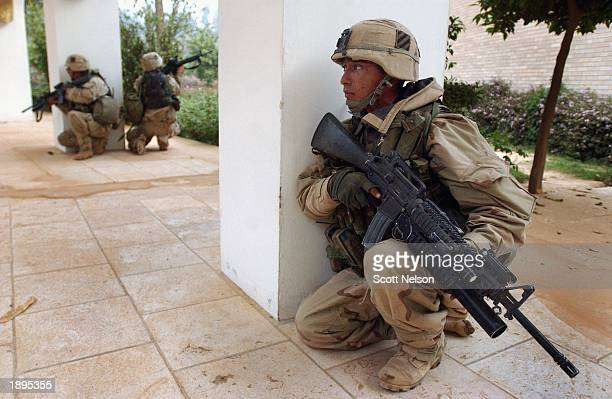 S Army 3rd Division 37 Corporal Edwin Garcia from Los Angeles CA takes cover outside the VIP terminal of Baghdad International Airport during a April...