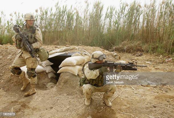 S Army 3rd Division 37 infantry soldier Corporal Edwin Garcia from Los Angeles CA provides cover as Sergeant Matthew Gadzalinski from Milwaukee WI...