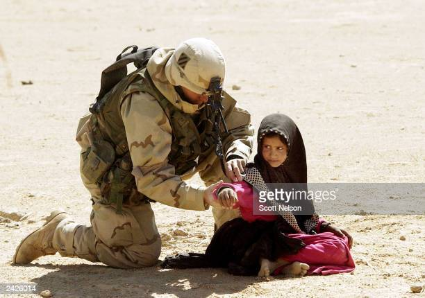 S Army 3rd Division 37 Infantry soldier searches an Iraqi girl during a search and destroy mission March 27 2003 near the town of An Najaf Iraq The...