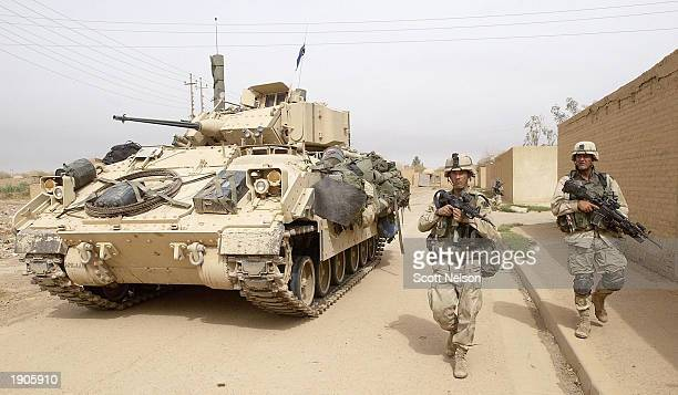 Army 3rd Division 3-7 infantry soldiers use a Bradley fighting vehicle for cover as they conduct a neighborhood patrol on the outside perimeter of...