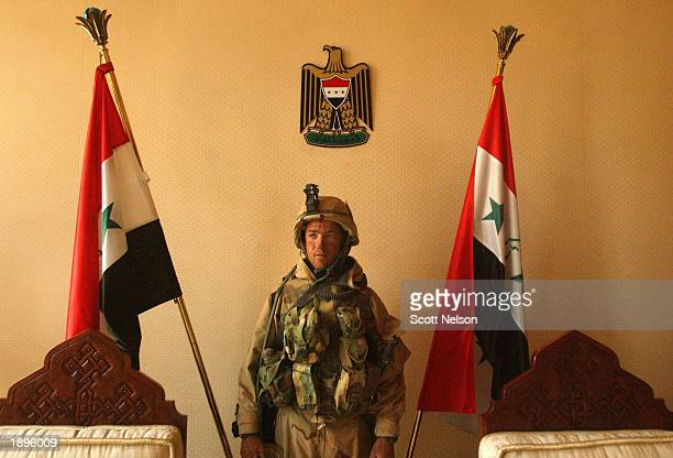S Army 3rd Division 37 Second Platoon Leader Lieutenant Mike Washburn from Yorktown Virginia jokingly poses in front of Iraqi flags after leading his...
