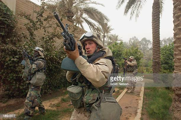 S Army 3rd Division 37 Specialist John Earle from Weymouth MA advances with his squad towards the VIP terminal of Baghdad International Airport...