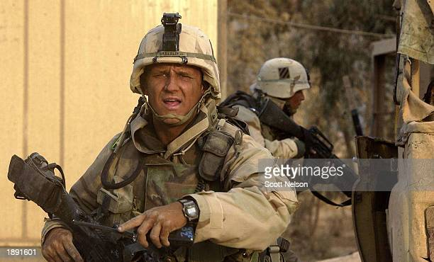 S Army 3rd Division 37 Task Force Sergeant Matthew Gadzalinski from Milwakee Wisconsin directs his squad April 2 2003 as they clear a captured Iraqi...