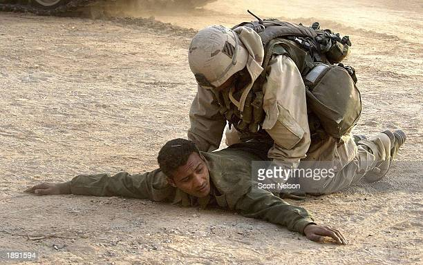 S Army 3rd Division 37 Task Force soldier takes a surrendering Iraqi soldier into custody April 2 2003 at a captured Iraqi army outpost in the...