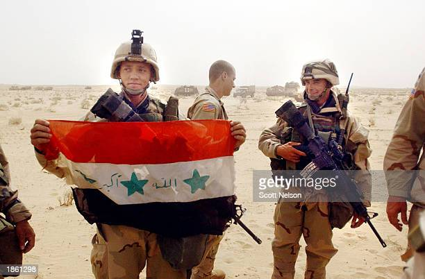 S Army 3rd Infantry Division 37 infantry Corporal Charles Johnson from Myrtle Beach South Carolina shows his squad an Iraqi flag captured during an...