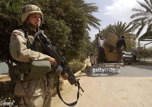 S Army 3rd Infantry soldier watches as Iraqis loot Saddam Hussein's former palace near the Baghdad International Airport April 10 2003 in downtown...
