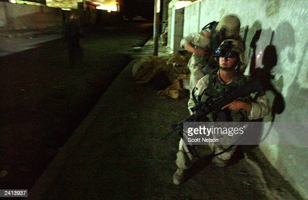 Army 4th Infantry Division 1-12 pause to radio in their present position during a nighttime foot patrol of the city center August 21, 2003 in...