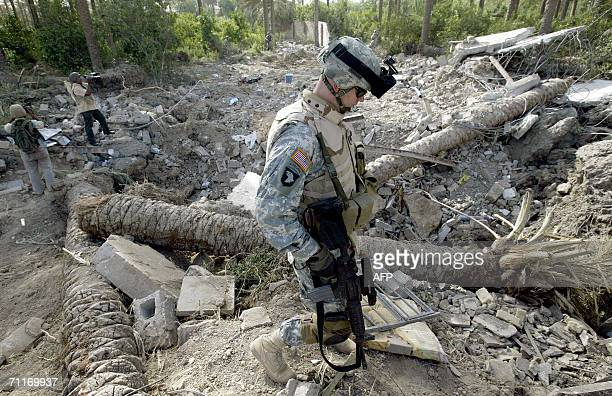 S Army 4th Infantry Division soldier walks past a crater at the scene of the recent airstrike airstrike against alQaeda leader in Iraq Abu Musab...