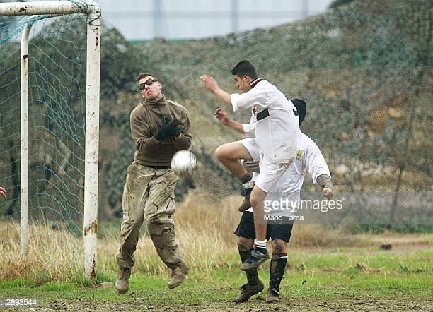 S Army 519th Military Police Battalion Spc Joseph Layman of Alton Illinois battles an Iraqi traffic police officer in a friendly soccer match January...