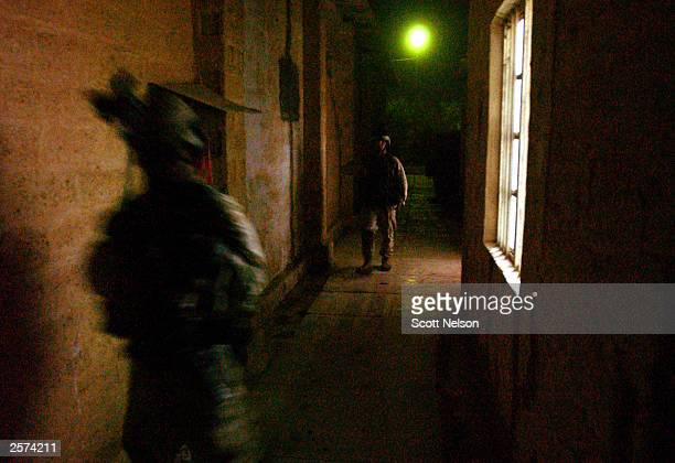 S Army 82nd Airborne Division 1st battalion 504th regiment soldiers move down a dark alley between two buildings during building sweeps on an October...