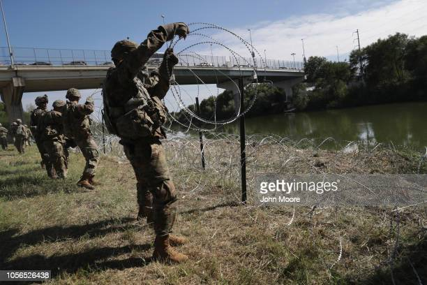 S Army active duty troops from Ft Riley Kansas 97th MP Battalion install protective wire along the Rio Grande at the USMexico border on November 2...