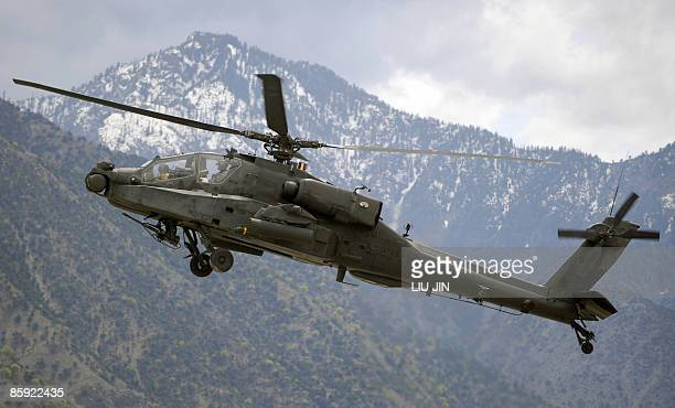 Army AH-64 Apache helicopter flies over the ISAF's Camp Bostick in Naray, in the eastern Kunar province on April 13, 2009. US President Barack Obama,...