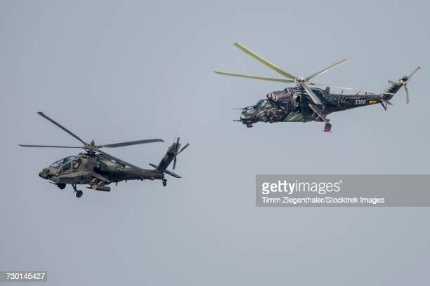 a u.s. army ah-64d apache and a czech air force mi-24 training in the czech republic. - apache helicopter stock pictures, royalty-free photos & images