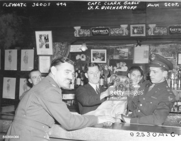 US Army Air Corps Capt Clark Gable and Lt R Dieckerhoff pose with a dog and unidentified patrons at an embarkation point bar England 1944 The men...