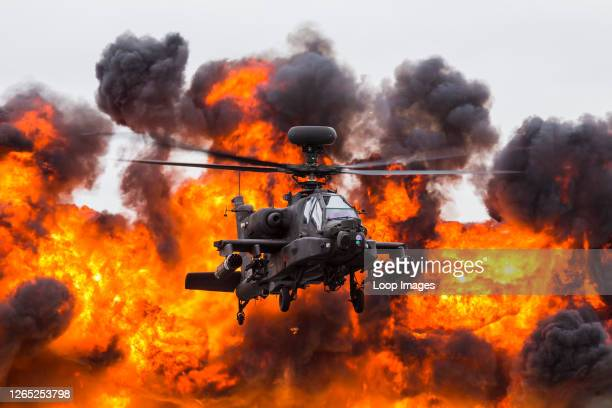 Army Air Corps WAH-64D Apache in front of a wall of fire.