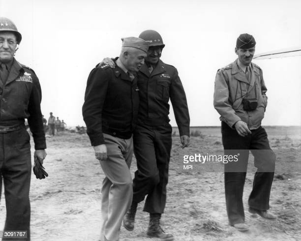 Army Air Forces General Henry 'Hap' Arnold and Lt General Omar Bradley of the US Ground Forces in the European Theatre of Operations walk along a...