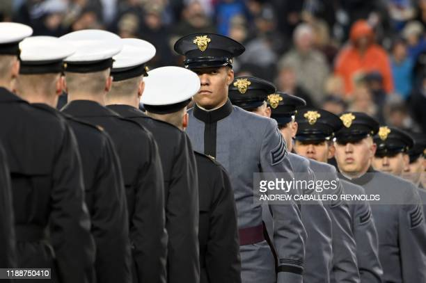 Army and Navy members meet half way as US President Donald Trump attends the ArmyNavy football game in Philadelphia Pennsylvania on December 14 2019