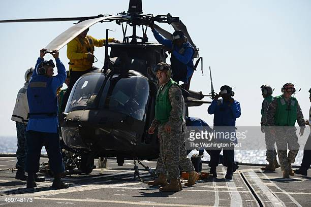 Army and Navy personnel work on a Bell OH58 Kiowa helicopter after Army pilots safely landed the aircraft on board the USS Lake Erie CG70 a...