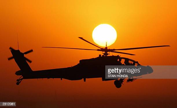 Army Apache attack helicopter from the 1501 Attack 4th Brigade 1st Armored Division flies in front of the rising sun in this aerial view 24 July 2003...