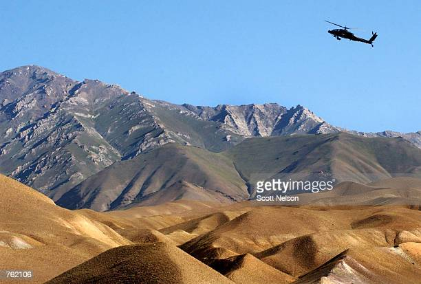 S Army Apache helicopter gunship gains altitude to clear a portion of the Baba mountain range June 17 2002 near Bamian Afghanistan Coalition forces...