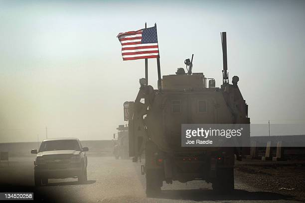 Army armored vehicle flies an American flag as it provides security escort for a convoy of vehicles pulling equipment that is heading to Kuwait from...