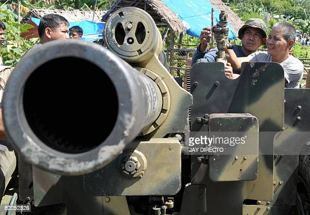 Army artillery men adjust angle as they fire a 105 mm Howitzer canon into Moro Islamic Liberation Front positions in Aleosan North Cotabato Province...