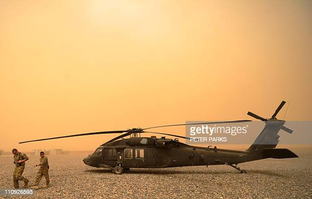 US army aviators from Alpha Company 7101 AVN walk away from their Blackhawk helicopter during a sandstorm at FOB Wilson in Kandahar province in...