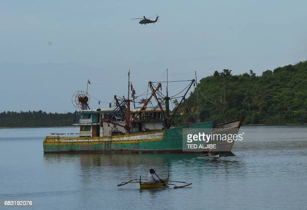 A US army black hawk helicopter flies over fishing vessels during a simulation of a disaster drill as part of the annual joint PhilippinesUS military...