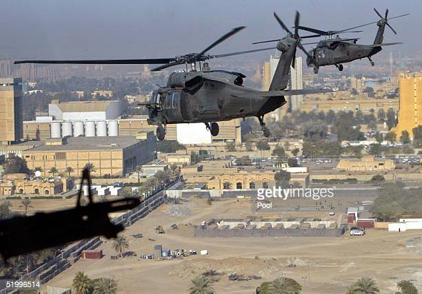 S Army Black Hawk helicopters fly over Baghdad as they carry Iraq's Prime Minister lyad Allawi to meet with residents January 15 2005 in the northern...