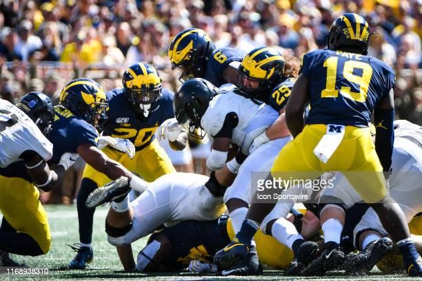 Army Black Knights quarterback Kelvin Hopkins Jr is tackled by Michigan Wolverines linebacker Jordan Glasgow and Michigan Wolverines linebacker Josh...