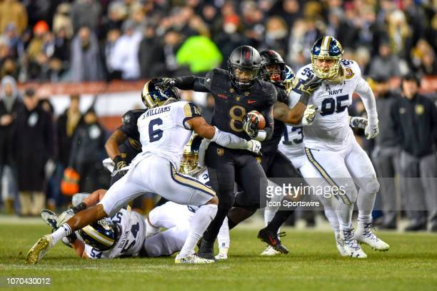 Army Black Knights quarterback Kelvin Hopkins Jr pushes his way past Navy Midshipmen safety Sean Williams and heads up the middle during the football...