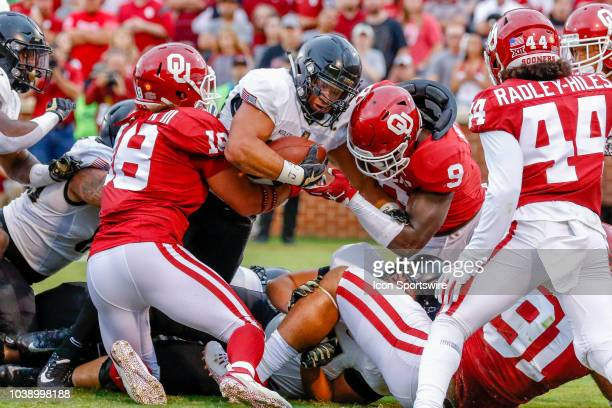 Army Black Knights running back Jordan Asberry center is stopped by Oklahoma Sooners linebacker Curtis Bolton and linebacker Kenneth Murray during...
