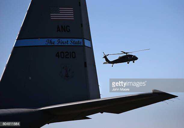 S Army Blackhawk helicopter passes an Air Force C130 cargo plane on the tarmac on January 10 2016 at a base in an undisclosed location in the Persian...