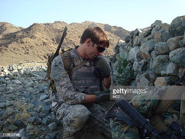 US Army Capt William Swenson of Seattle Washington calls for air support on his radio as they take cover after Afghan security forces and their US...