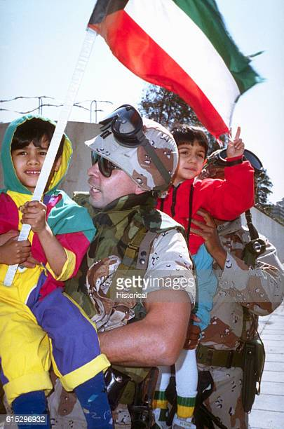 A US Army captain holds up a girl waving a Kuwaiti flag as civilians and coalition military forces celebrate the retreat of Iraqi forces from Kuwait...
