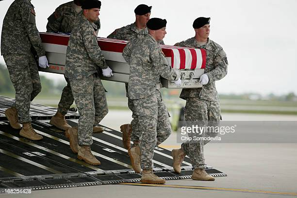 S Army carry team carries the flagdraped transfer case with the remains of Army 1st Lt Brandon Landrum off of a C17 on the tarmac at Dover Air Force...