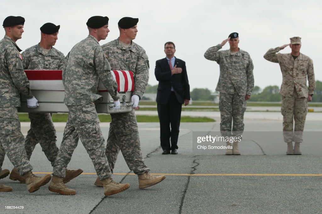 S. Army carry team carries the flag-draped transfer case with the remains of Army 1st Lt. Brandon Landrum across the tarmac at Dover Air Force Base as (L-R) Deputy Secretary of Defense Ashton Carter, Army Maj. Gen. William Rapp and Marine Col. Christian Cabaniss salute May 7, 2013 in Dover, Delaware. A member of the 1st Brigade Combat Team, 1st Armored Division, Landrum and four other soliders were killed May 4 when their vehicle hit a roadside bomb during a patrol in the Maiwand District in Kandahar Province, Afghanistan.