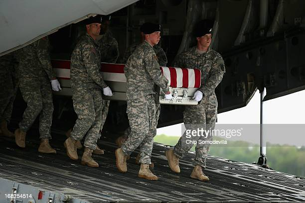 S Army carry team carries the flagdraped transfer case with the remains of Army Staff Sgt Francis Phillips IV of Meridan New York off of a C17 on the...