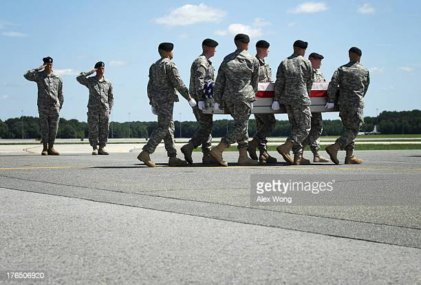 S Army carry team carries the flagdraped transfer case with the remains of Army Sergeant Jamar A Hicks of Little Rock Arkansas across the tarmac...